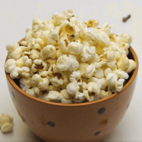 small brown bowl of popcorn filled with pumpkin spice popcorn